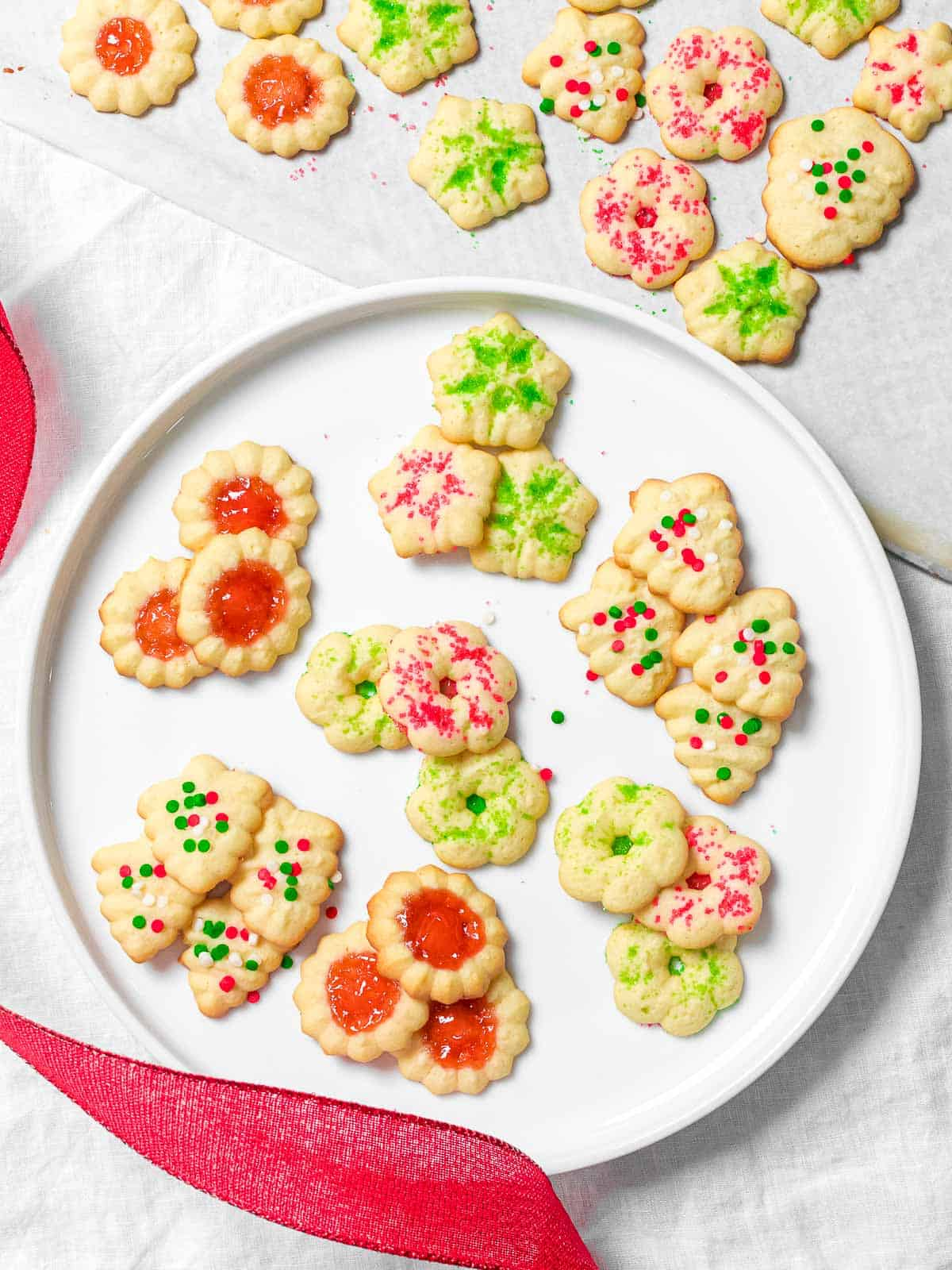 Christmas cookie press cookies decorated with red and green Christmas sprinkles on a white plate.
