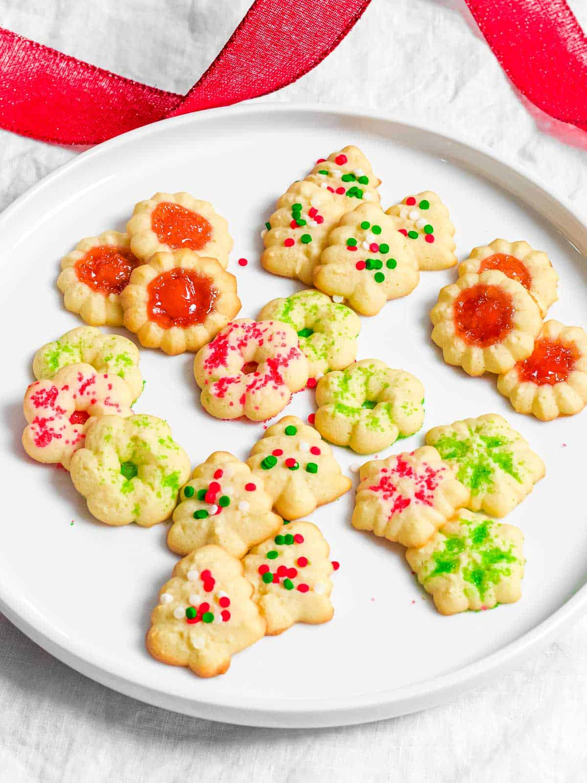 Christmas spritz cookies in the shapes of Christmas trees, snowflakes, and wreaths decorated with red and green sprinkles on a plate.
