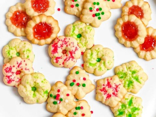 Christmas spritz cookies with red and green Christmas sprinkles on a plate.