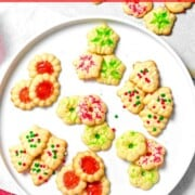Christmas spritz cookies in snowflake, wreath, and Christmas tree shapes with sprinkles.