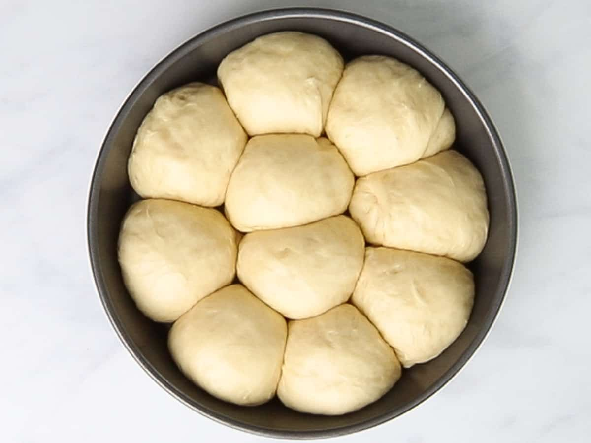 Brioche rolls proofing in a round baking pan until it doubles in size.