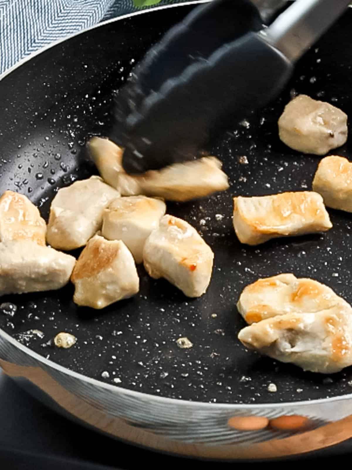 Chicken being stir fried in a pan.