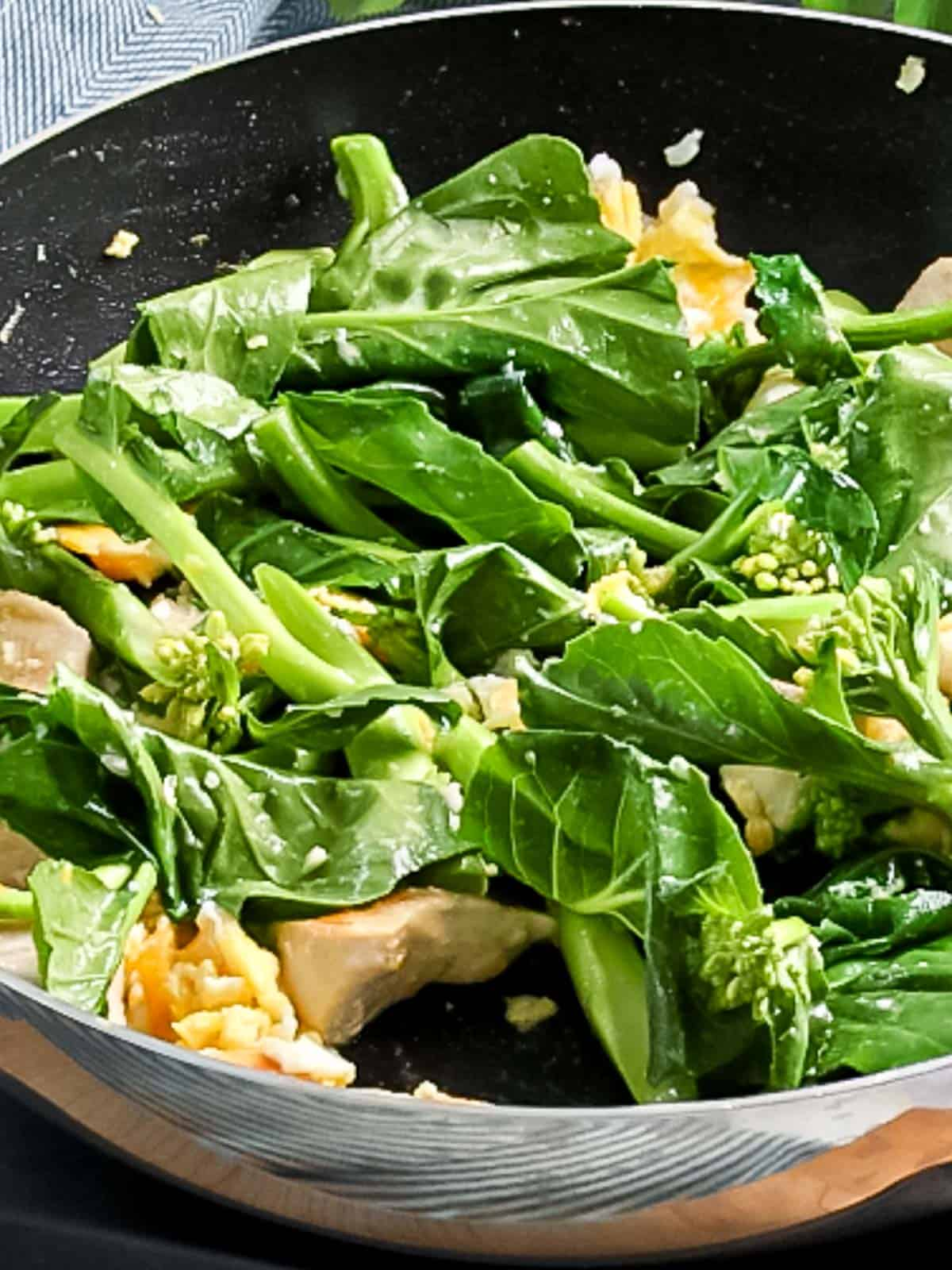 Chinese broccoli (gai lan) added to fried eggs and chicken.