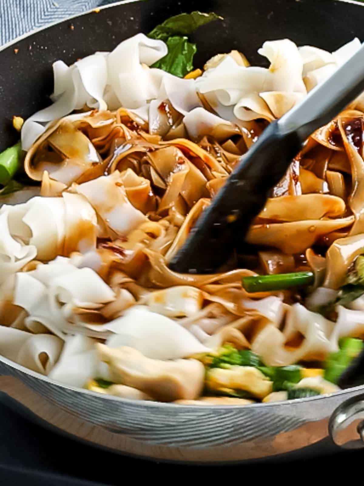 Wide rice noodles and pad see ew sauce being stir fried together with Chinese broccoli.