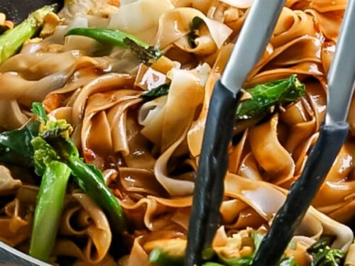Wide rice noodles and Chinese broccoli being tossed together with pad see ew sauce until mixed together.