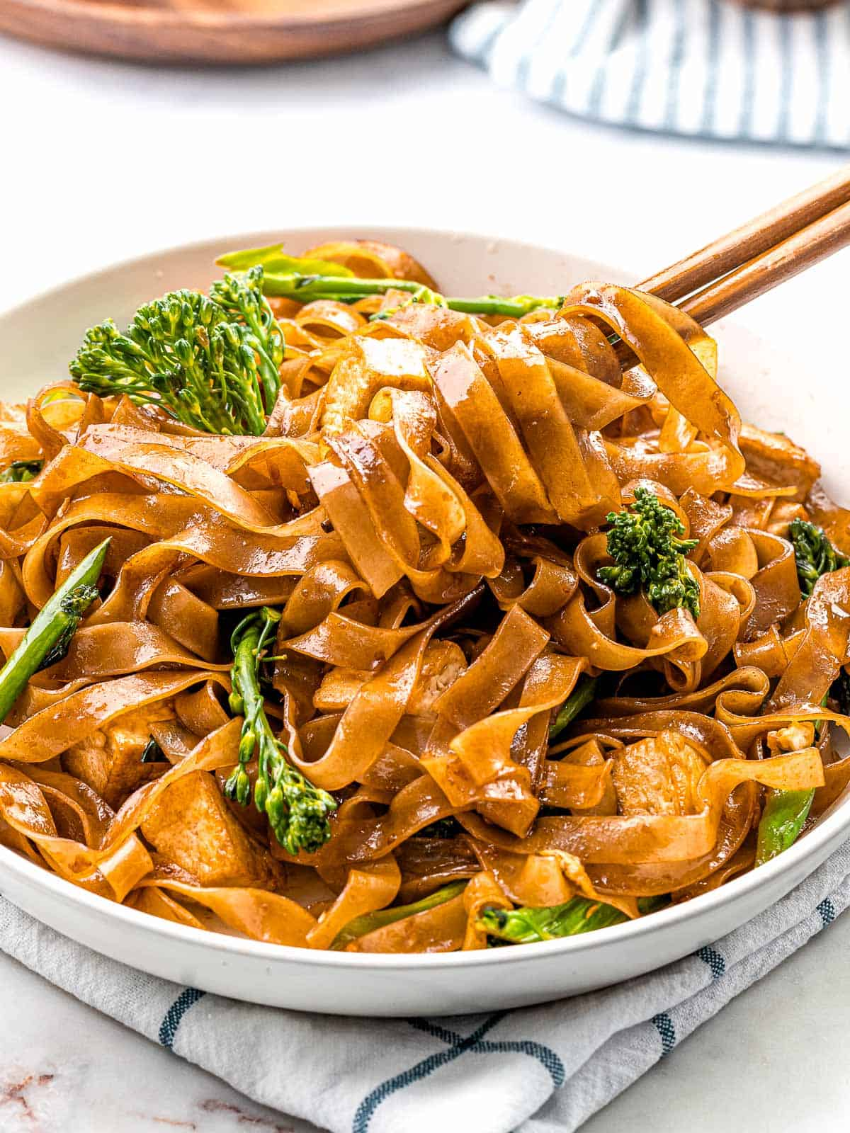 Pad see ew noodles stir fried with Chinese broccoli and chicken wrapped around chopsticks.