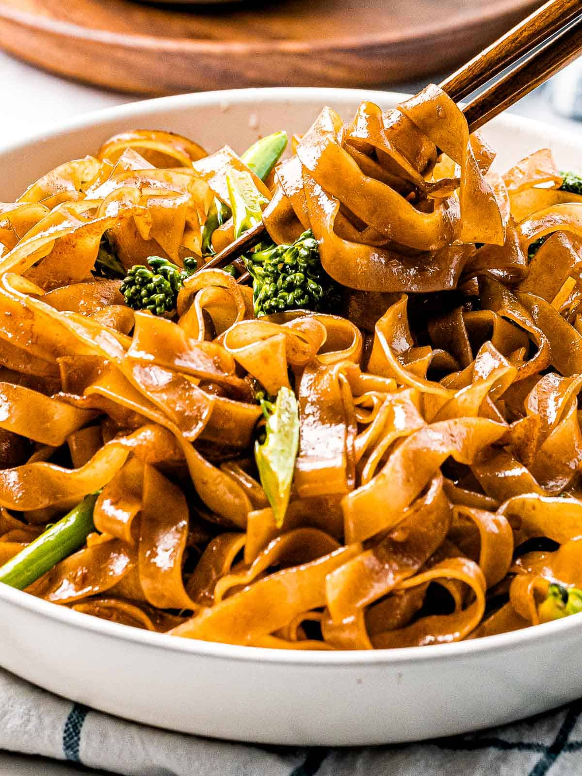 Pad see ew noodles stir fried until caramelized with Chinese broccoli wrapped around chopsticks.