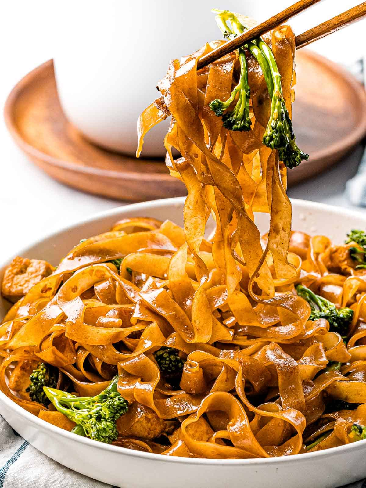 Pad see ew noodles stir fried in sauce with Chinese broccoli held up by chopsticks.
