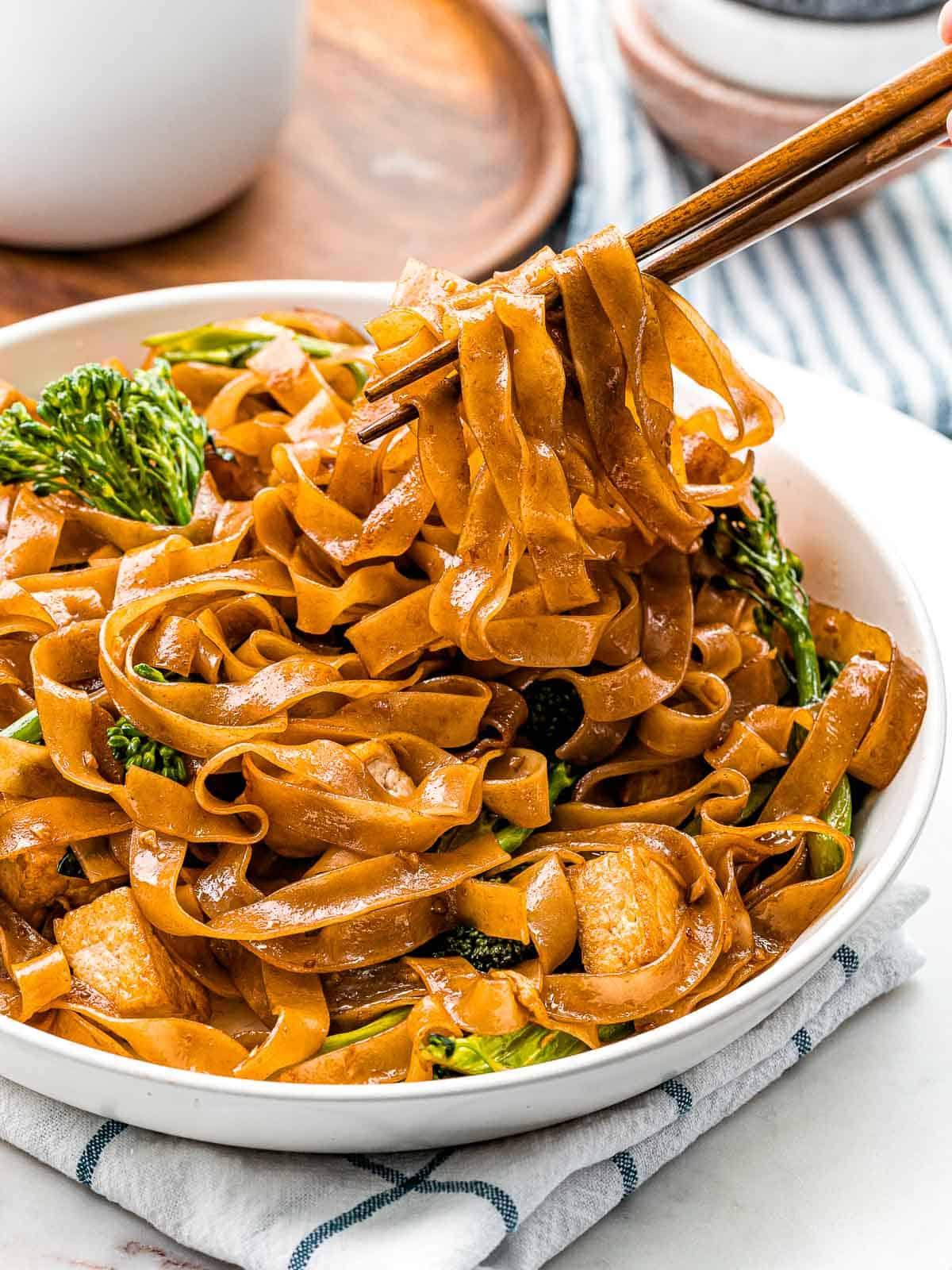 Pad see ew noodles held by chopsticks.