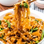Pad see ew noodles with chicken and broccoli held up by chopsticks.