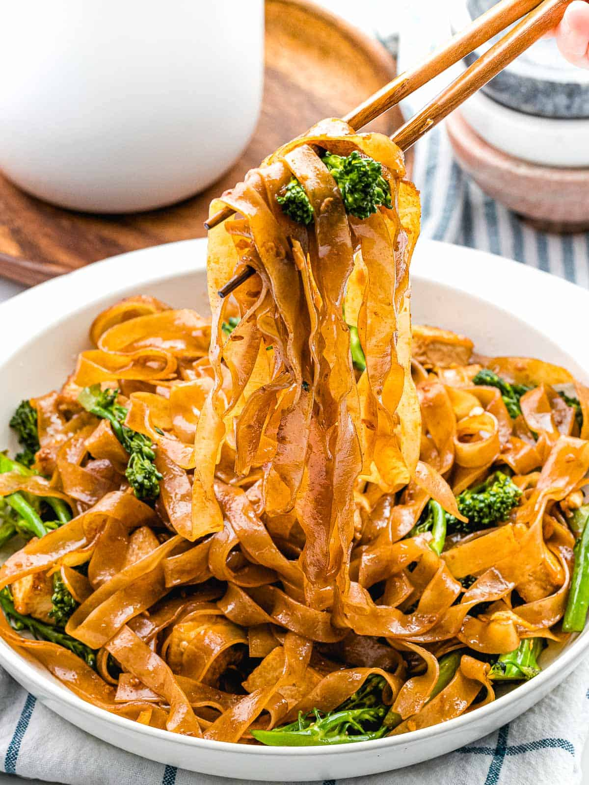 Pad see ew (ผัดซีอิ๊ว) stir fried noodles with broccoli and egg held by chopsticks.