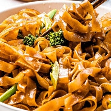 Pad see ew noodles (ผัดซีอิ๊ว) wrapped around chopsticks.
