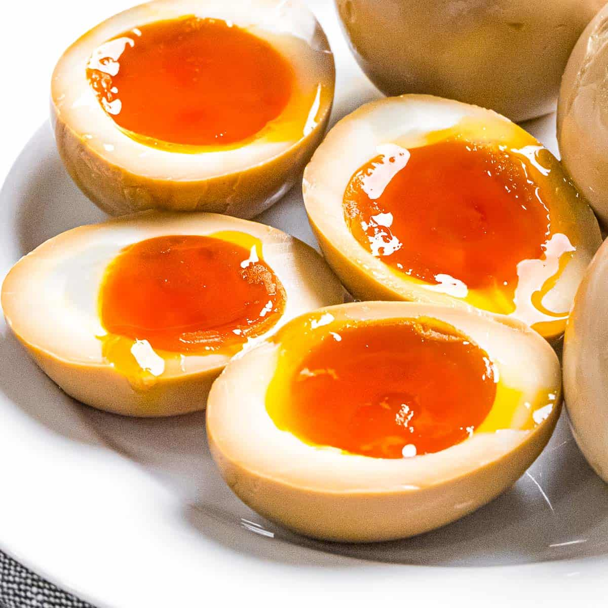 Ramen eggs marinated in soy sauce cut in half to reveal soft boiled eggs with runny yolks.