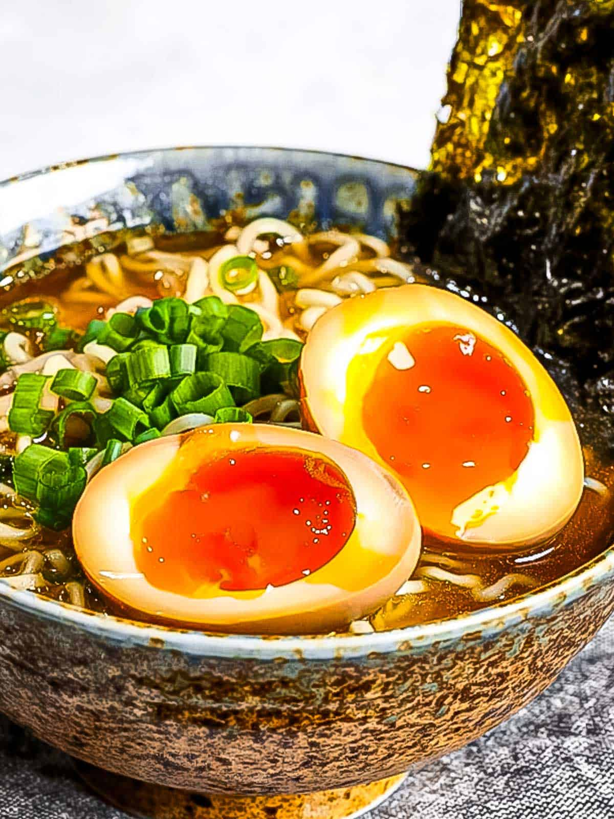 Ramen eggs (ajitama) marinated in soy sauce cut in half and placed on top of a bowl of ramen noodles garnished with green onions and nori.