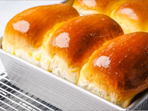 Milk bread loaves baked in the oven with golden brown crust.