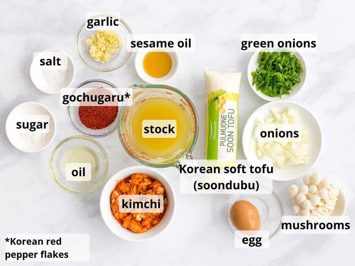 Ingredients for soondubu jiggae including soon tofu, broth, kimchi, and mushrooms.