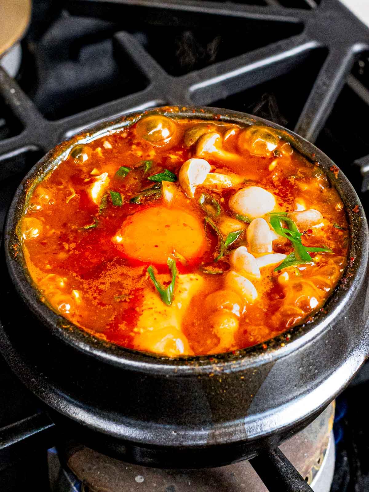Korean tofu soup or soondubu jiggae with mushrooms and egg in an earthenware pot.