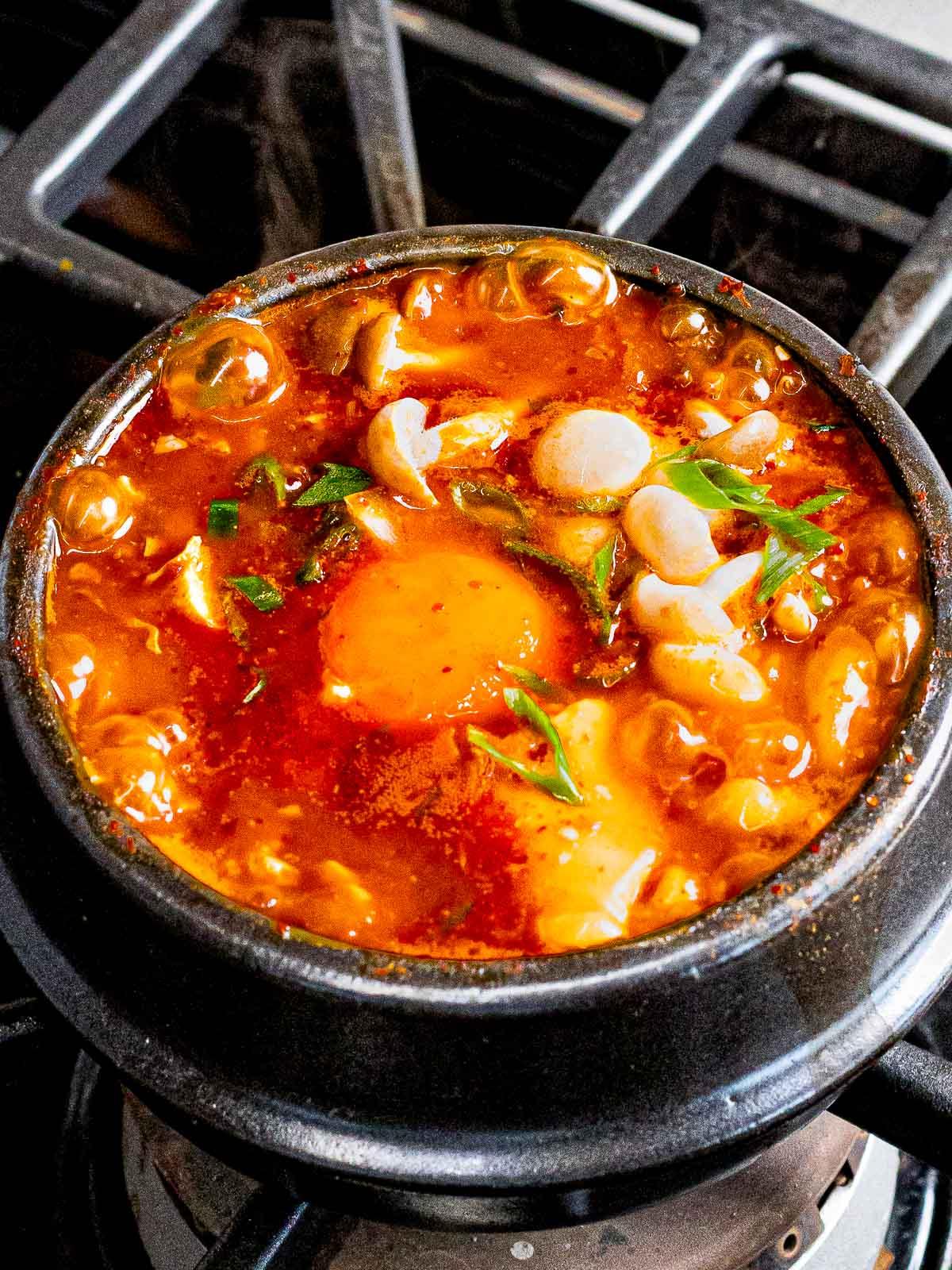 Soondubu jiggae (spicy Korean soft tofu soup) with mushrooms, egg, and green onions.