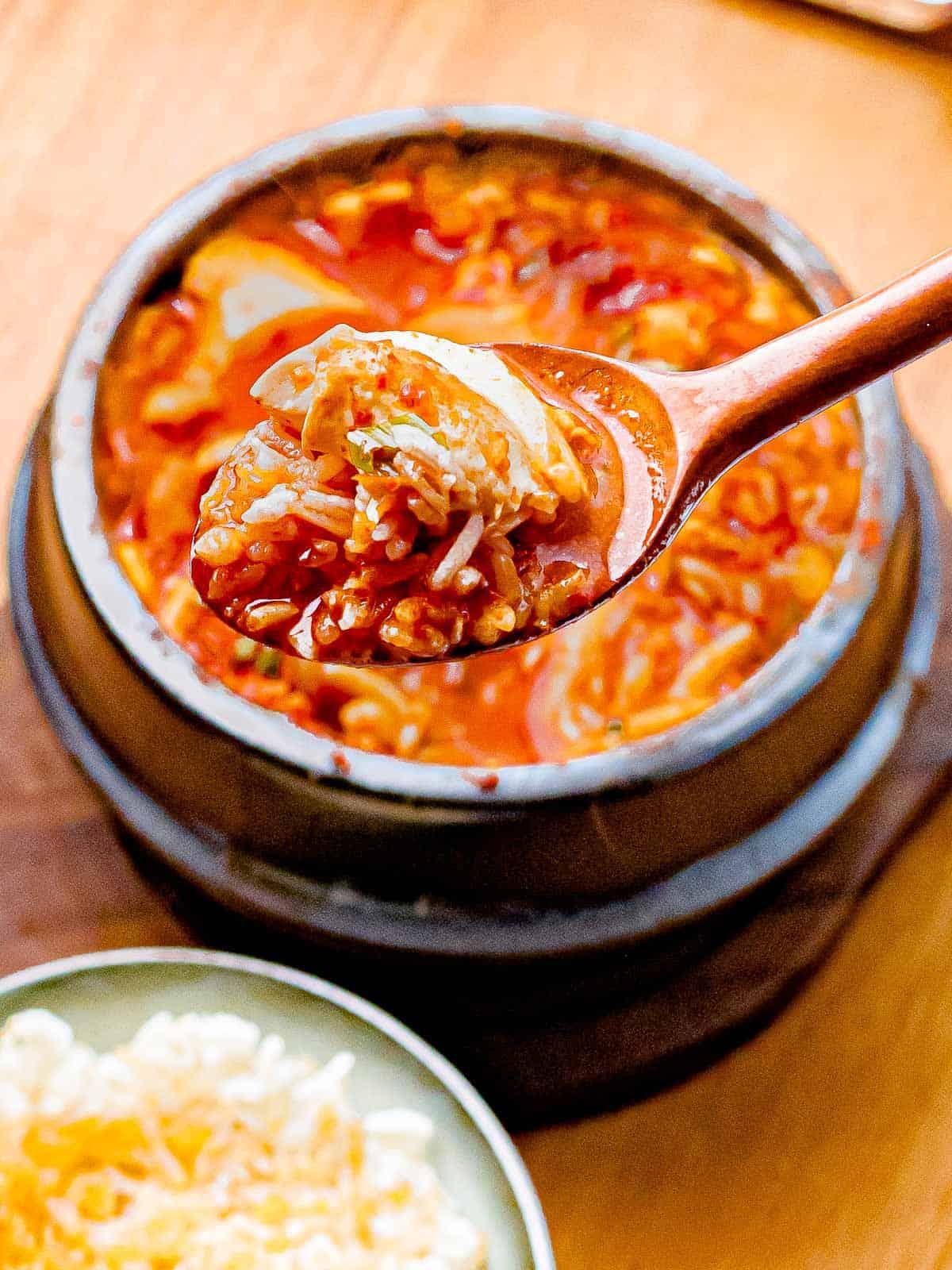Spoonful of soondubu jiggae with rice.