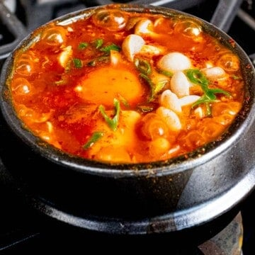 Soondubu jjigae with mushrooms, soft tofu, and egg cooking in an earthenware pot.