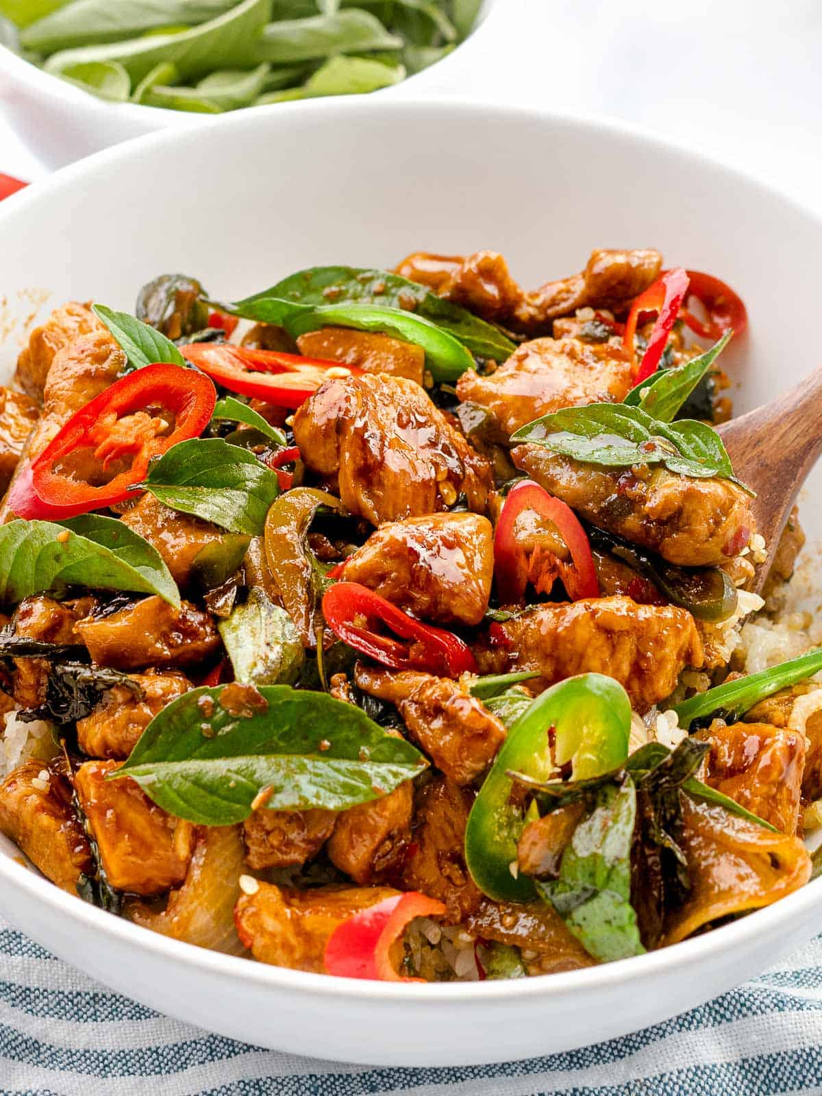 Thai basil chicken (pad krapow gai) with fresh basil leaves and red pepper slices.