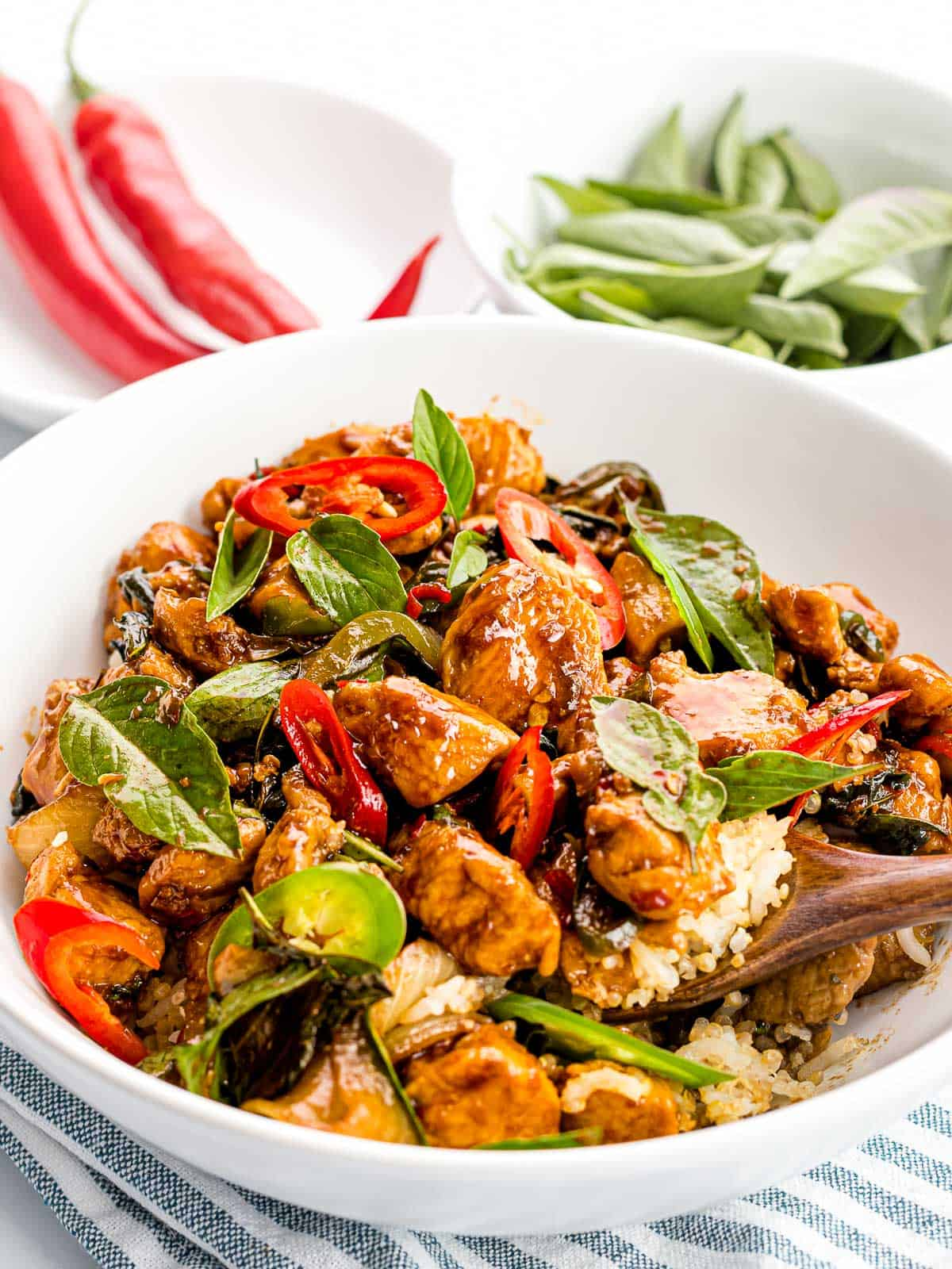 Thai basil chicken stir fried with red chili peppers in a bowl with rice.