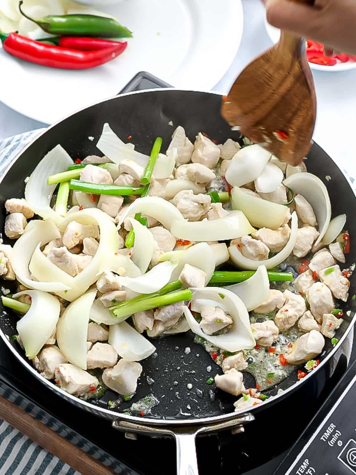 Chicken, onions, and green onions stir frying in a pan.