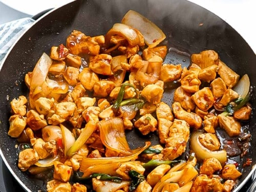 Chicken stir frying in a pan with sauce.