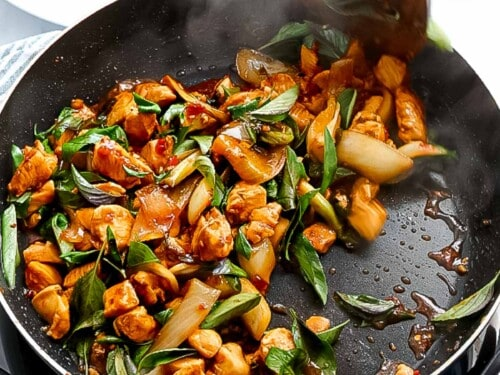 Thai basil leaves stir frying with chicken in a pan.