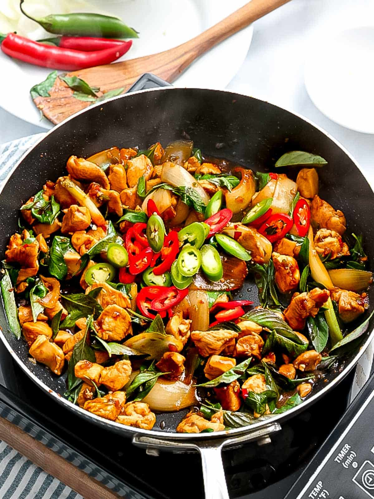 Thai basil chicken being stir fried in a pan with chili pepper slices.