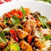 Thai basil chicken in a bowl with rice with text overlay.