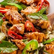 Thai basil chicken in a bowl with text overlay on red banner.