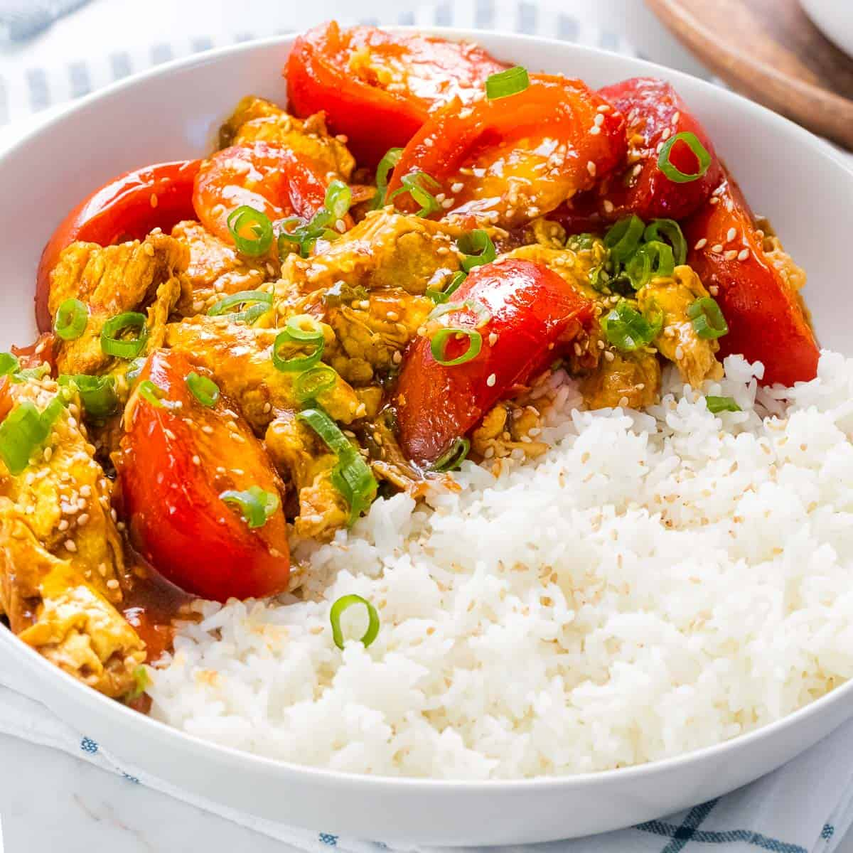 Chinese tomato egg stir fry in a bowl of rice.